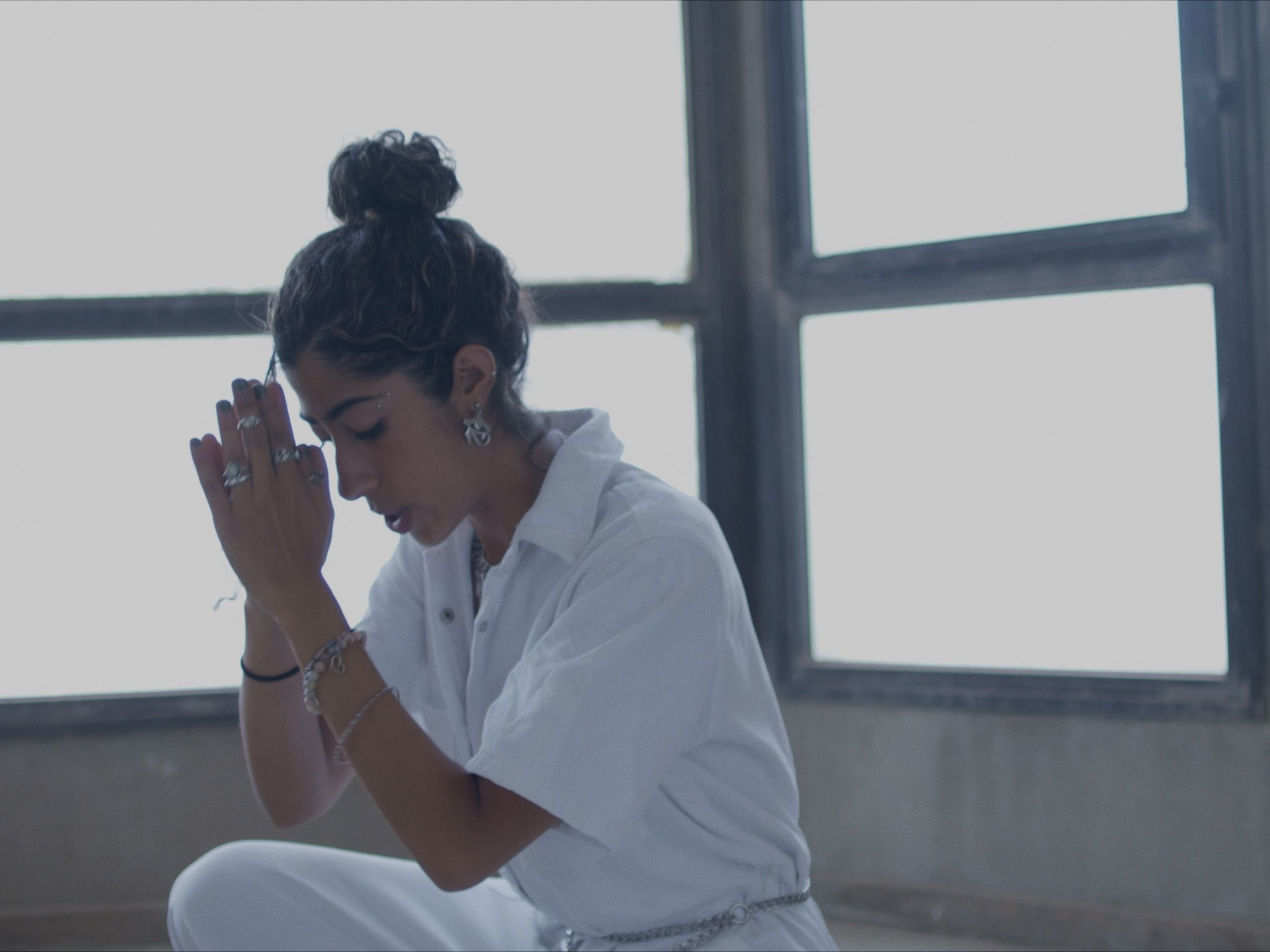 A woman in white sitting with her hands in prayer