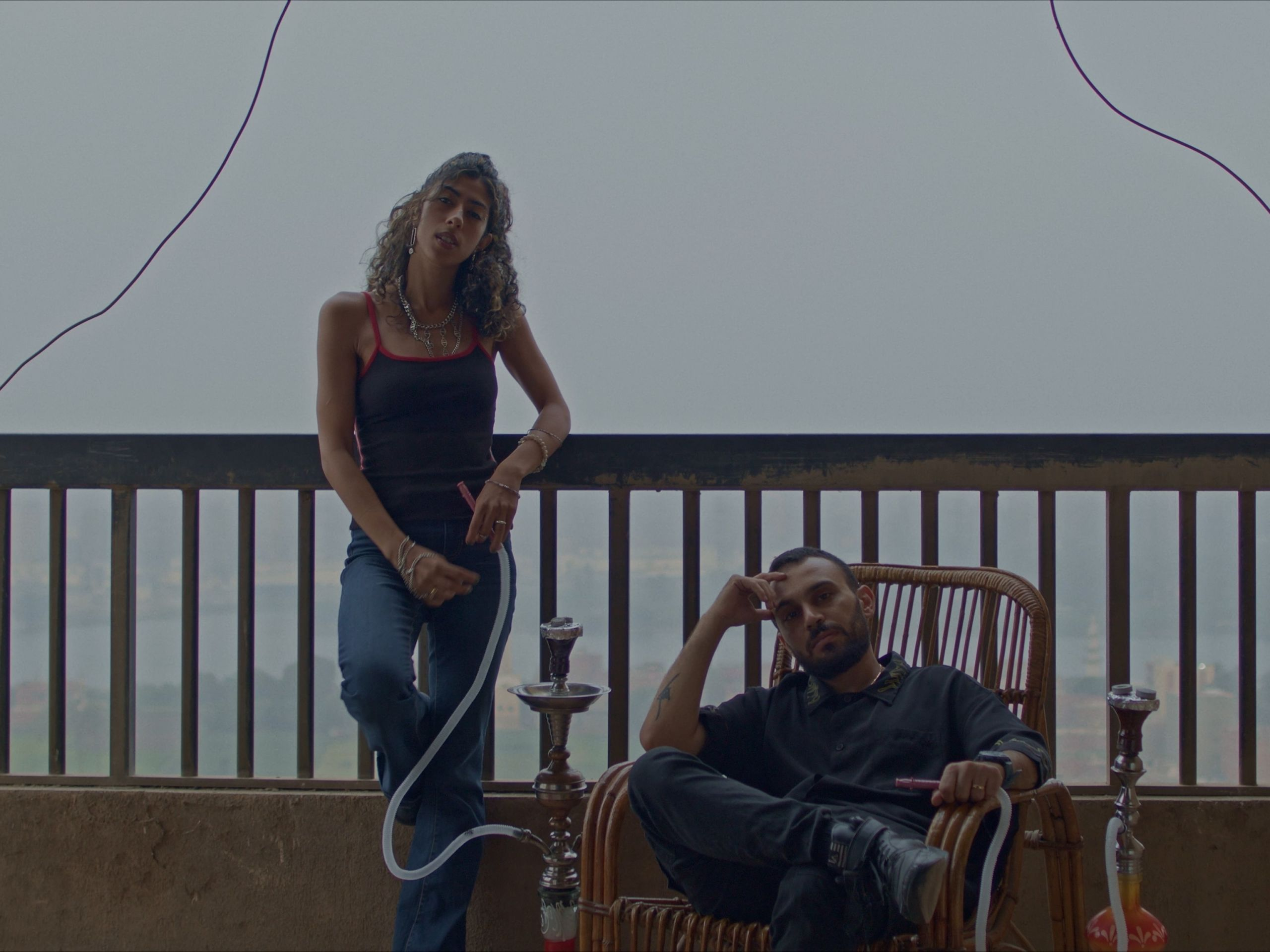 A portrait of a man and woman on a balcony. She is standing he is seated, both have shisha pipes.
