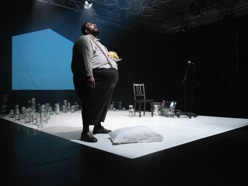 A large man standing on a darkly lit stage